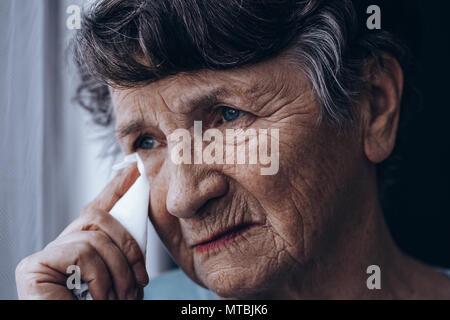 Portrait von Weinen ältere Frau, holding Gewebe
