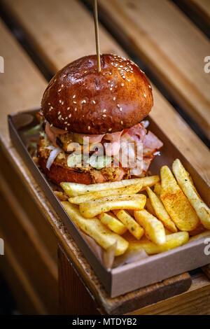 Beefburger mit gebratenen Zwiebeln, Speck und Pommes frites in brioche Bun - Stockfoto