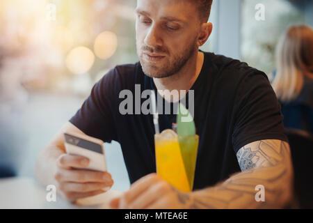 Attraktiven jungen Mann liest Nachricht an Handy und tranken Limonade. - Stockfoto