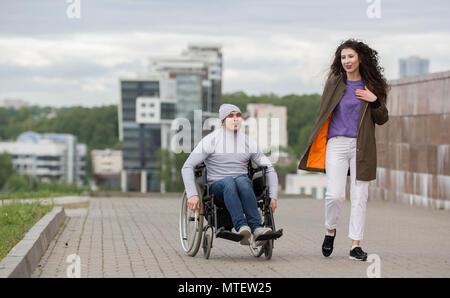 Glückliches Paar - behinderte junge Mann im Rollstuhl mit jungen Frau zusammen den Sonnenuntergang genießen. - Stockfoto