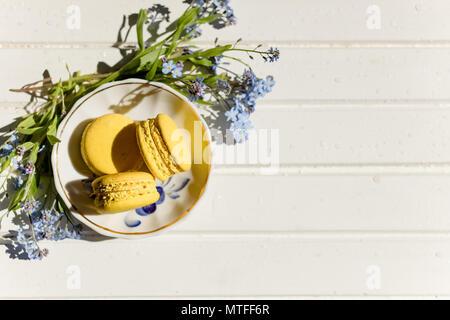 Leckere bunte Makronen auf trendy vintage Holztisch mit vergißmeinnicht Blumen und Konfetti, flach. Lecker gelb, Zitrone Makronen. Platz für Text. candy für die Partei. Getonten Bild - Stockfoto