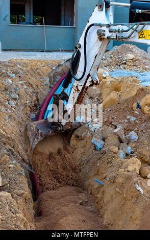 Bagger elektrische Leitungen mit Hilfe eines Arbeitnehmers mit Sand ...