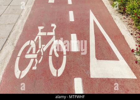 Radweg. Fahrrad unterzeichnen und weiße Pfeil auf dem roten Asphalt Pfad - Stockfoto