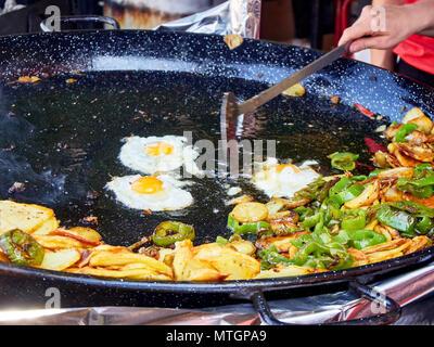 Spanische Eier im Gange. Gebratene Eier mit Kartoffeln und Paprika in der Pfanne. Spanisch Street Food.