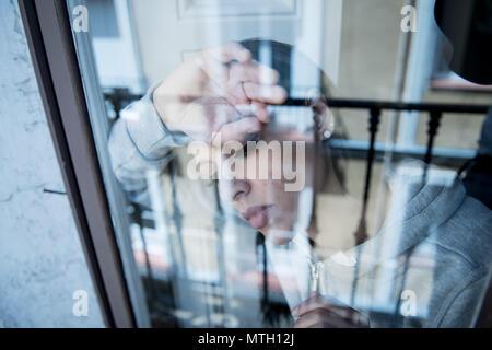 Junge schöne depressiv unglücklich Latin Frau besorgt und traurig durch das Fenster zu Hause. Gefühl, wertlos und Schmerzen. closeup. Depression ein - Stockfoto