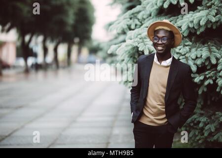 Stattliche Afro-amerikanische Mann in Freizeitkleidung und Sonnenbrillen zu Fuß draußen auf der Straße - Stockfoto