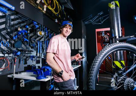 Eine junge, elegante rothaarigen Mann Small Business Owner verkauf und reparatur ein Fahrrad trägt eine blaue Kappe und ein rosa Trikot ist mit einem Handy whil - Stockfoto