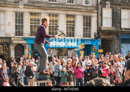 Männliche Street Performer Jonglieren ein Messer und Äxte während Balancing vor große Menschenmenge auf der Royal Mile in Edinburgh, Schottland, Großbritannien