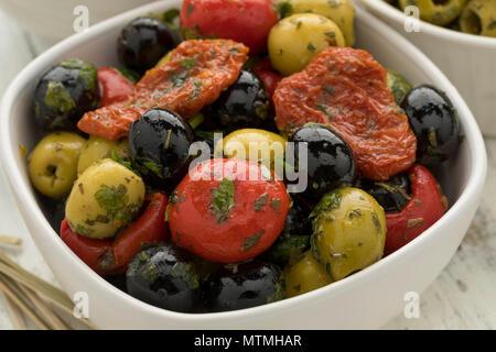 Schüssel mit grünen und schwarzen Oliven, Paprika und Tomaten als Snack Nahaufnahme - Stockfoto