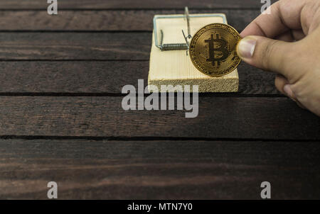 Holz- Maus Trap und Mann hält Bitcoin - Stockfoto