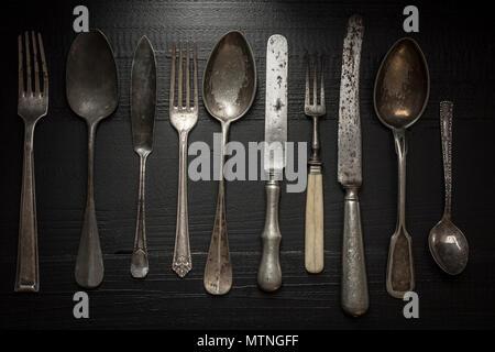 Alte rustikale Besteck auf dunklem Hintergrund. Küche und Essen Konzept. - Stockfoto