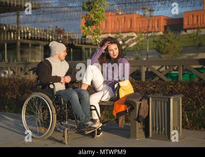 Junge Frau mit behinderten Menschen im Rollstuhl am Kai Sonnenlicht genießen. - Stockfoto