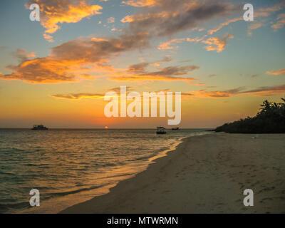 Malediven Hintergrund. Sonnenuntergang über dem tropischen Meer und Coral Beach mit bunten Wolken im Himmel. Boote am Horizont in der himmlischen Atoll der Ruhe und Entspannung. Nord Male Atoll Asdu, Indischer Ozean. - Stockfoto