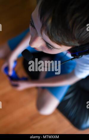 Ein Teenager mit einem Headset und Mikrofon, während die Playstation PS4 online zu kommunizieren, seine Teamkollegen im Spiel Fortnite. - Stockfoto