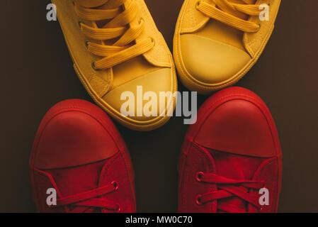 Junges Paar auf eine liebe Datum, konzeptionelle Bild. Blick von oben auf die zwei Paar lässige Sneakers, Gelb und Rot, von oben in der Nähe und nach einander wie - Stockfoto