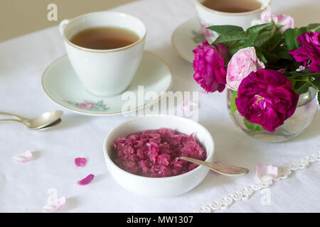Stau in die Blütenblätter der Damaskus Rose, eine Tasse grünen Tee und eine Vase mit Rosen auf einem Leuchttisch. Rustikaler Stil, selektiven Fokus. - Stockfoto
