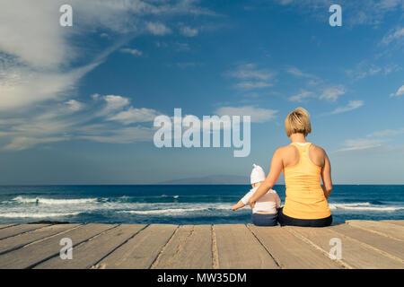Baby Junge spielt mit der Mutter am Strand, Sommer Tag. Supermom mit toddlersohn Entspannen auf Holz- Strand Bürgersteig. Auf inspirierende Landschaft. - Stockfoto