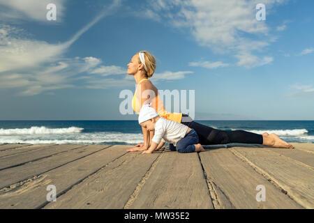 Baby Junge spielt mit der Mutter am Strand, Sommer Tag. Supermom mit Kleinkind Sohn lernen Yoga auf Holz- Strand Bürgersteig. - Stockfoto