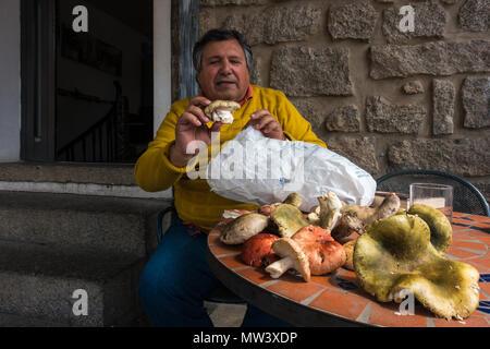 Italienischen Mann mit einer Tüte hat essbare Pilze auf dem Display vor einem Cafe in Sardinien - Stockfoto