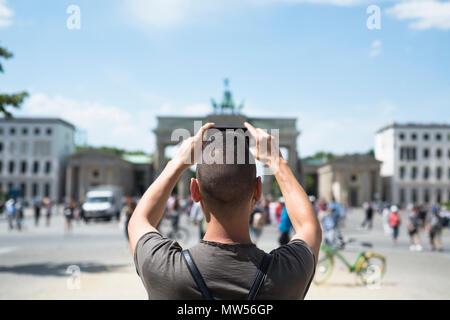 Nahaufnahme eines jungen kaukasischen Mann, von hinten gesehen, ein Bild von der beliebten Brandenburger Tor in Berlin, Deutschland, mit seinem Smartphone - Stockfoto