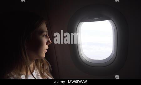 Junge Mädchen auf der Ebene schaut aus dem Fenster. Mädchen schaut aus dem Fenster eines fliegenden Flugzeug. Junge Passagiere reisen mit dem Flugzeug, beobachten den Himmel von oben. Travel Concept - Stockfoto