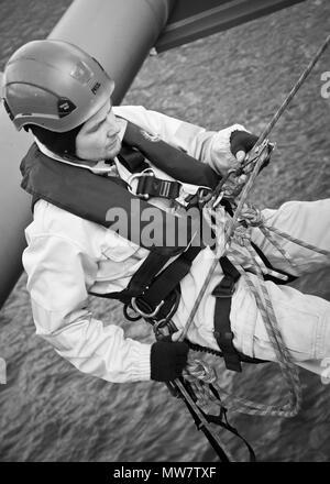 Schwarz-Weiß Nahaufnahme Bild von Mann suchen entspannt und sich sicher, in hoher Sichtbarkeit Überlebensanzug gekleidet, lehnt sich nach hinten über dunkles Wasser. - Stockfoto