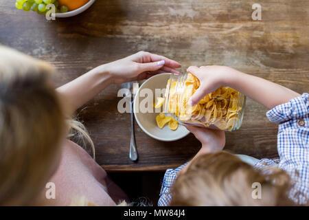 Ansicht von oben von Mutter und Sohn Vorbereitung corn flakes zum Frühstück - Stockfoto