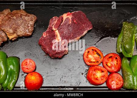 Rib Eye Steak (spanisch: Bife Ancho) roh und gegrillt, Tomaten und grüne Paprika auf rechteckiger Gusseisen flache Pfanne, flach legen - Stockfoto