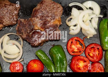 Rib Eye Steak (Spanisch: Bife ancho), Zwiebeln, Tomaten und Paprika gegrillt auf einem Gusseisen Rechteck Griddleplatte, flach - Stockfoto