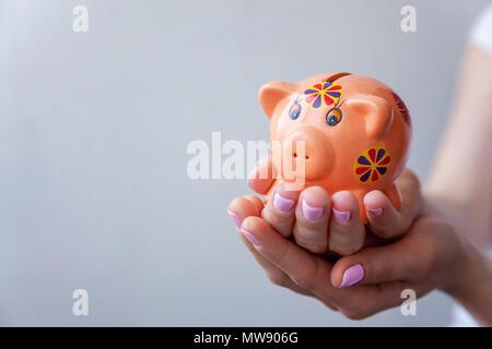Frau hand Halten rosa Sparschwein. Speichern Investitionsbudget Reichtum business Ruhestand Konzept - Stockfoto
