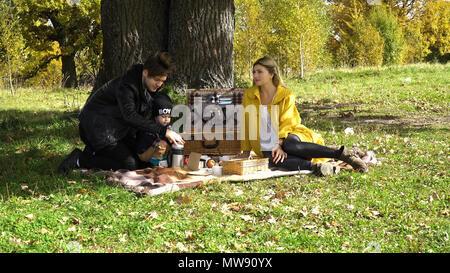Junge Familie mit Sohn beim Picknick im Park an einem sonnigen Tag. Familie mit Picknick im Freien. Junge lächelnde Familie tun, ein Picknick auf einer Herbst Tag. Familie Picknick zusammen. - Stockfoto
