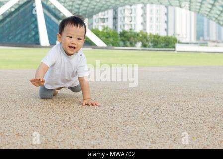 Asiatische baby boy Kriechen in Park - Stockfoto