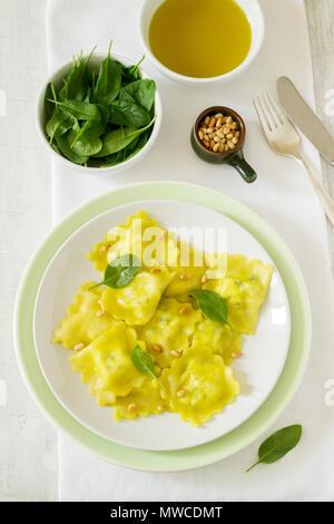 Ravioli mit Ricotta und Spinat, serviert mit Olivenöl und Pinienkernen. Im rustikalen Stil. - Stockfoto
