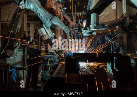 Industrieroboter sind Bewegung Schweißen automotive Teil im Werk - Stockfoto
