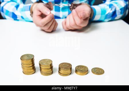 Es gibt Gold Münzen auf den Tisch, im Hintergrund ein Mann in Handschellen. Finanzielle Probleme, Diebstahl, Unterschlagung, Betrug. Geld pro