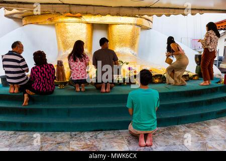 Die Gläubigen vor den Füßen eines Big Standing Buddha im Wat Intharawihan Tempel beten - Stockfoto