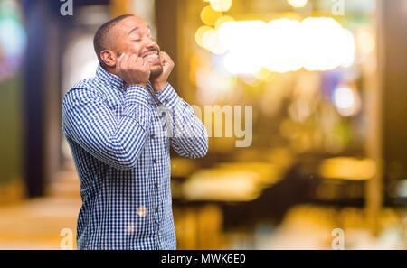 Afrikanische amerikanische Mann mit Bart zuversichtlich und zufrieden mit einen großen natürlichen Lächeln Lachen bei Nacht - Stockfoto