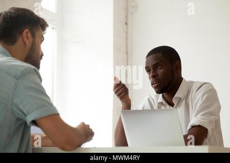 Schwere schwarze Arbeiter im Gespräch mit kaukasischen Kollegen während der BUSIN - Stockfoto