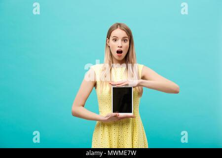 Aufgeregt gut - schockiert suchen junge Frau im gelben Kleid, verwirrt oder verwirrten Ausdruck auf dem Gesicht beim Empfang, dringende Nachricht oder E-Mail, mit Wi-fi auf Tablet. - Stockfoto