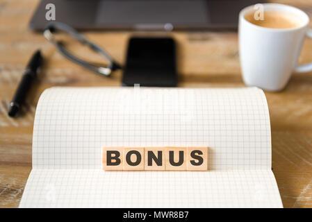 Nahaufnahme auf das Notebook um Holz Tisch Hintergrund, auf Holzblöcken mit Buchstaben, Bonus Text konzentrieren. - Stockfoto