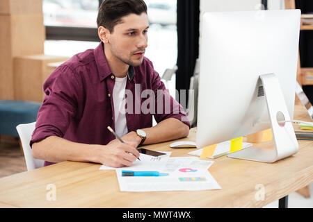Konzentrierte Geschäftsmann arbeiten am Computer am Arbeitsplatz im Büro - Stockfoto