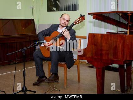 In der Music Hall ein Konzert Gitarrist. Ein junger Mann spielt Gitarre. - Stockfoto