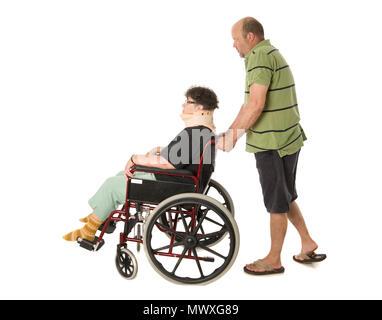 Ein reifer Mann drückte eine ältere Frau in einem Rollstuhl. - Stockfoto