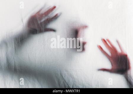 Beängstigend unscharfe Silhouette der unkenntlich Person hinter dem Schleier schreien - Stockfoto