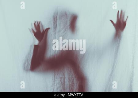 Beängstigend unscharfe Silhouette der Person Schleier mit den Händen berühren. - Stockfoto