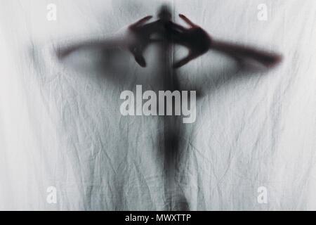 Unscharfe Silhouette der Person Vorhang mit den Händen berühren. - Stockfoto