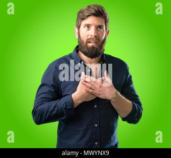 Junge hipster Mann mit großen Bart in charmanten Lächeln, Hände auf Herz, Liebe und Mitgefühl auf grünem Hintergrund anzeigen - Stockfoto