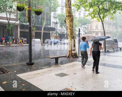 Menschen zu Fuß mit Sonnenschirmen im schweren Regen Sturm auf der Avenida de Mayo im Stadtzentrum Microcentro, Monserrat Bezirk in der Hauptstadt Buenos Aires, Argentinien - Stockfoto