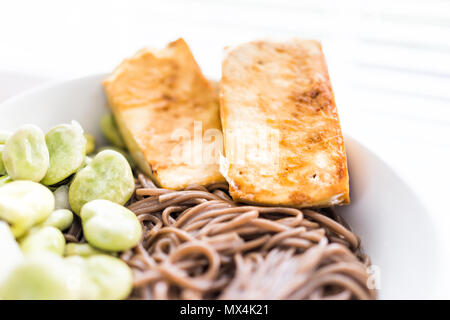 Soba Buchweizen Nudeln japanisches Frittiergut golden knusprig gebacken, Tofu, grüne Bohnen an heißen, kalten Sommer, weiße Schüssel Makro Nahaufnahme - Stockfoto