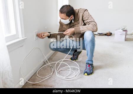 Junge Mann in der Maske installieren Fernsehen Kabel Internet Kabel im Zimmer an der Wand Teppichboden Bodenbeläge, weiße Wände, während Umbau Renovierung, Reinigung, ich - Stockfoto